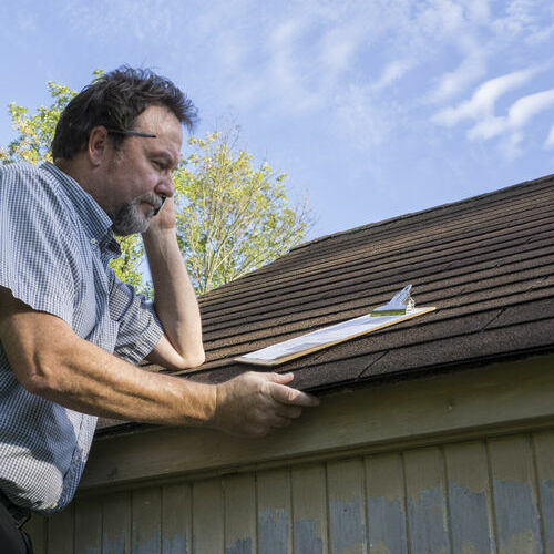 An Insurance Adjuster Inspects a Roof.